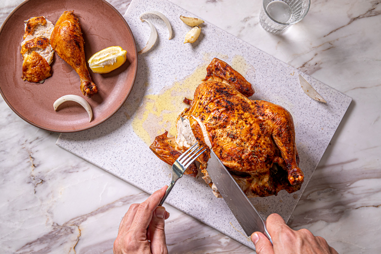 overhead view of a golden roasted chicken on a cutting board. Two hands are holding a knife and fork and carving into the chicken breast