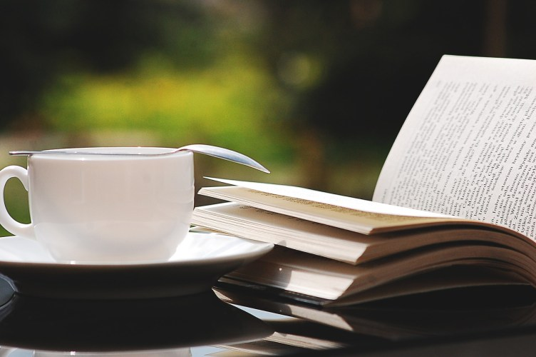 Welcome to Brewing Wisdom! Coffee and a book laying on a table in the summer sun.