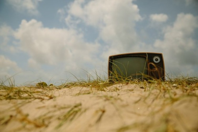 As for Me and My Home: An old Television set sitting derelict on a sand dune.