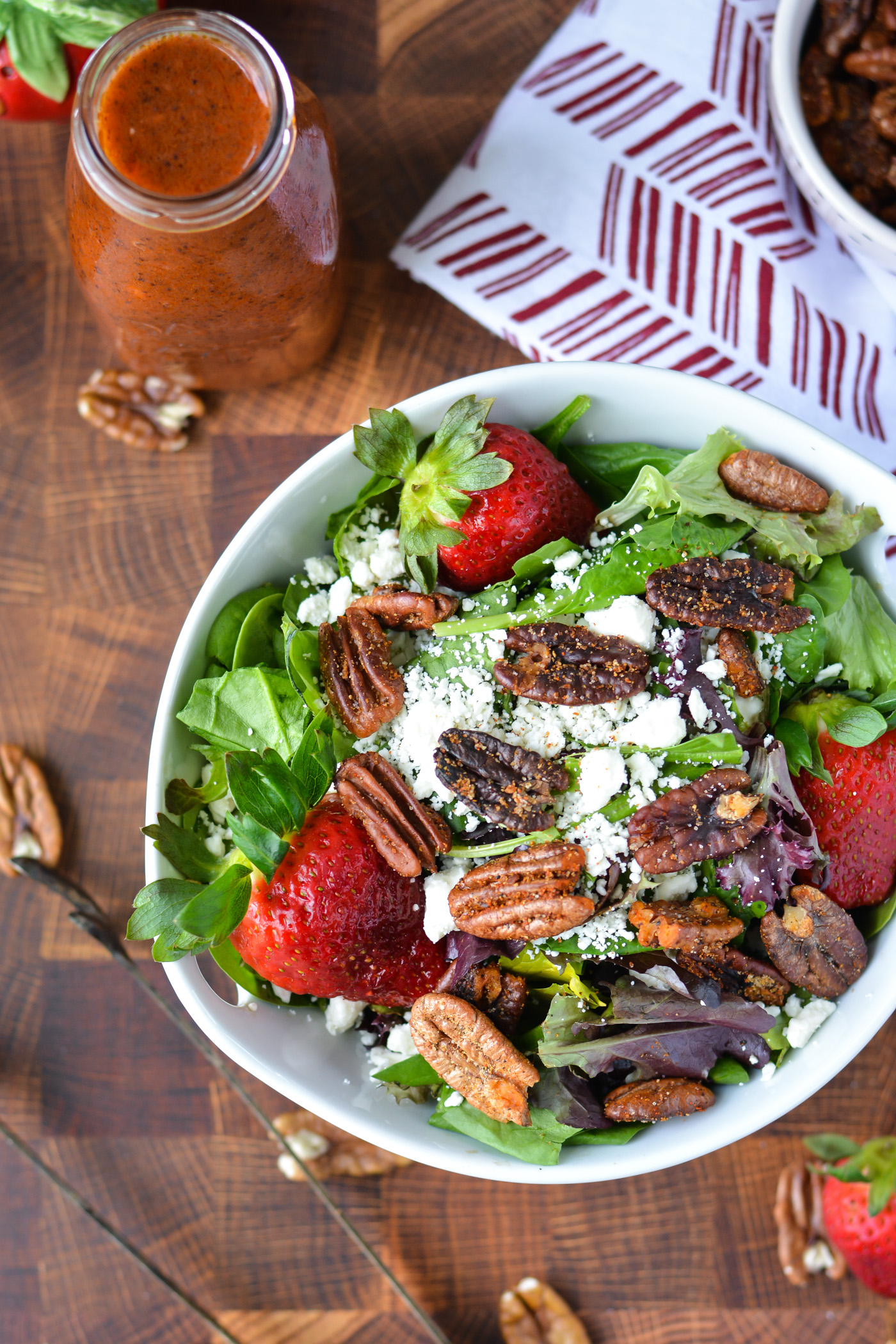 overhead shot of salad with mixed greens, fresh strawberries, feta cheese, and spiced pecans