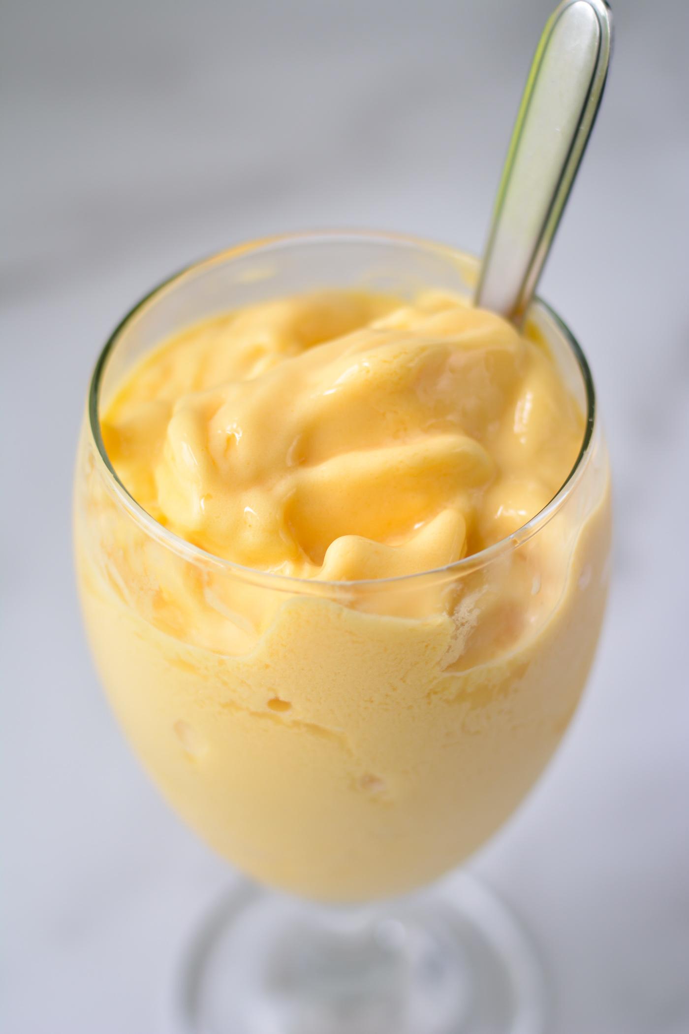bright golden mango kefir shake in glass goblet