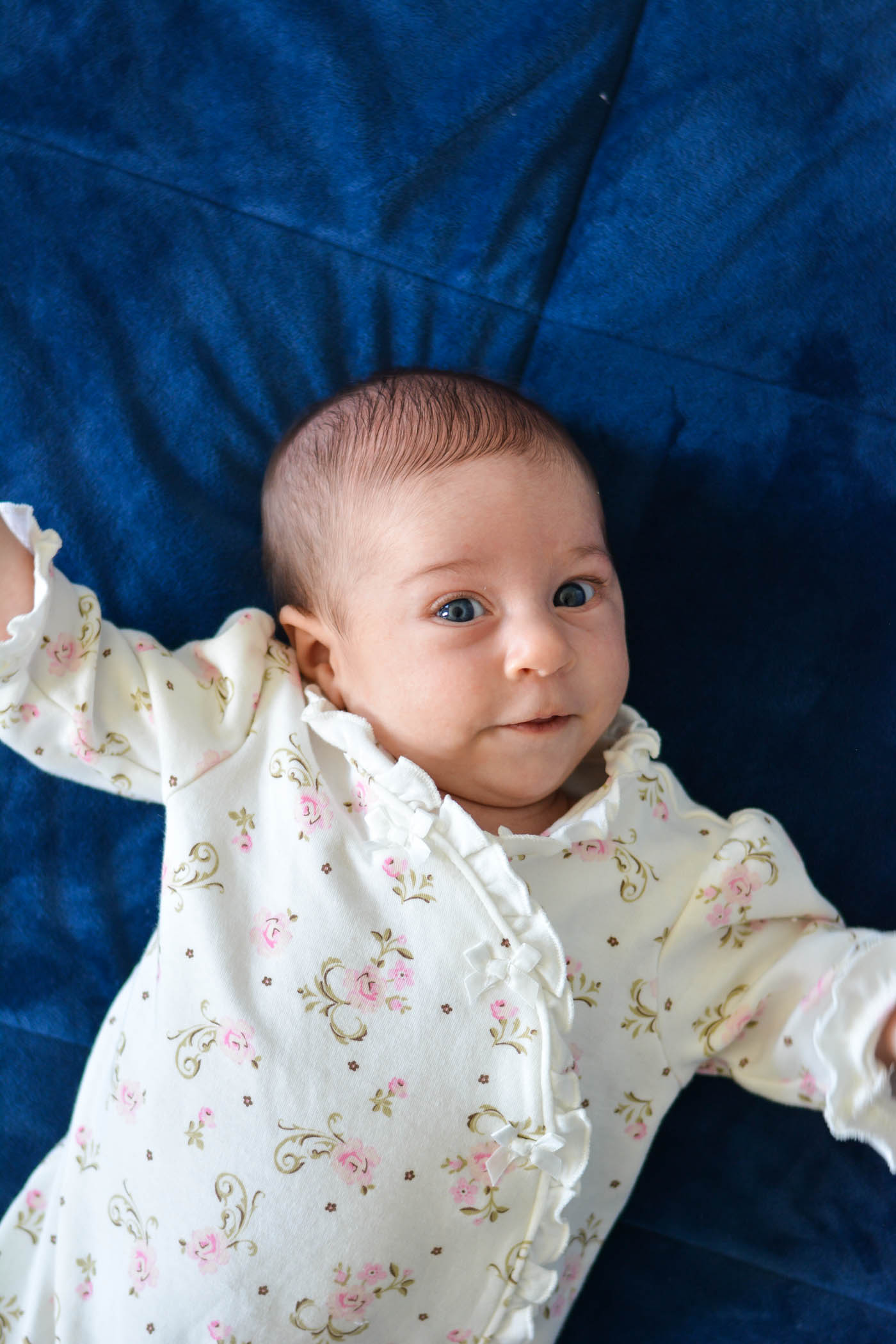 This is a picture of Hadassah lying on a velvety rich blue blanket, looking at the camera with big eyes, waving her arms, and half smiling. She's wearing a white sleeper with pink flowers on it.
