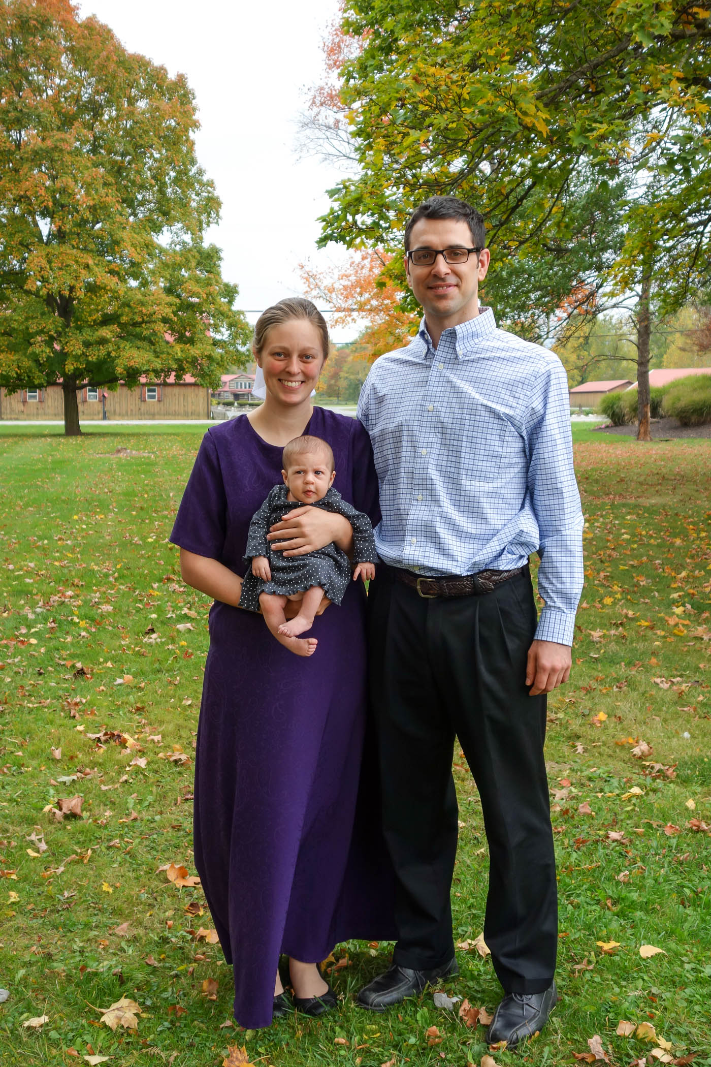 This is a picture of Ryan, Briana, and Hadassah standing outside on the grass with trees in the background. The trees are just starting to get some yellow leaves. Briana is wearing a royal purple dress, and Hadassah has a quirky expression on her face.