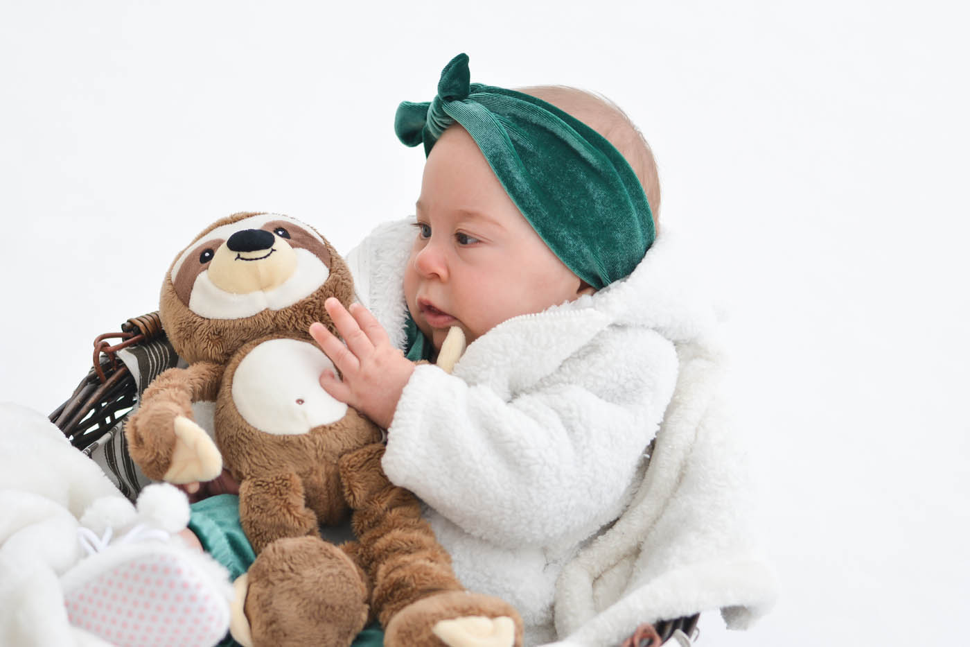 This is a picture of Hadassah holding a stuffed sloth toy. She's looking at it and reaching for its face with one hand.