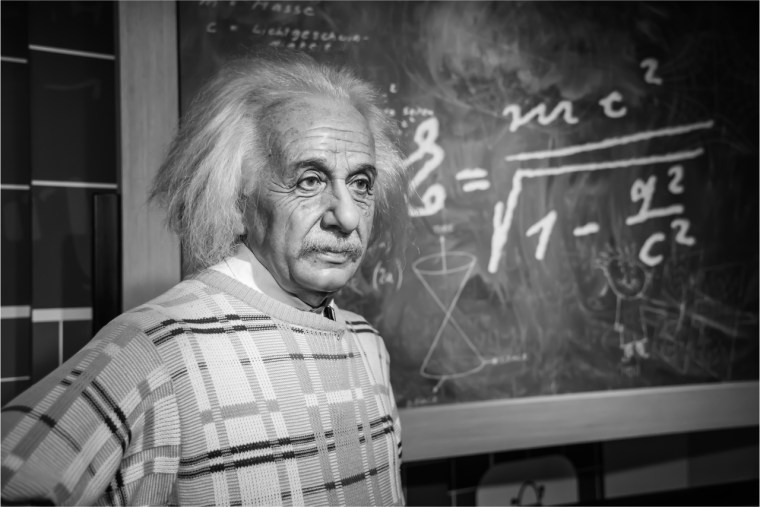 Einstein, a model of deep work, standing in front of a chalk board with an equation written on it