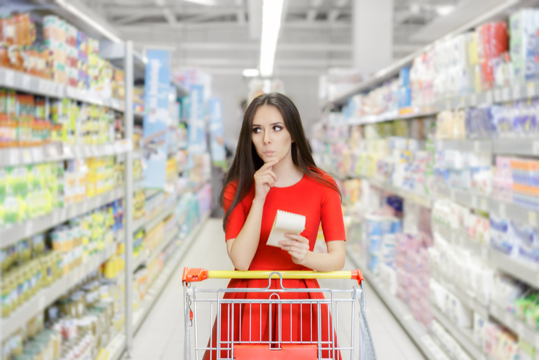 Woman in grocery store, contemplating which groceries to buy