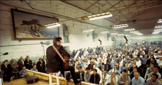johnny cash playing at folsom prison, photo taken from the stage perspective