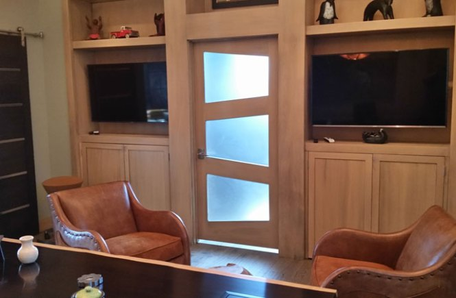 Custom door with trapezoid glass accents in a built in bookshelf