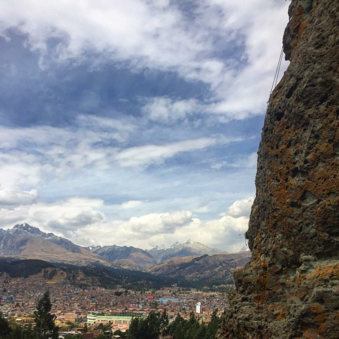 A climber on the wall in Los Olives. Huaraz in background.