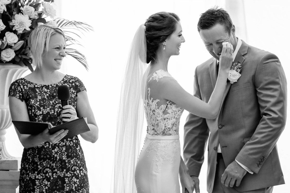 bride wiping tears from the groom while celebrant smiles