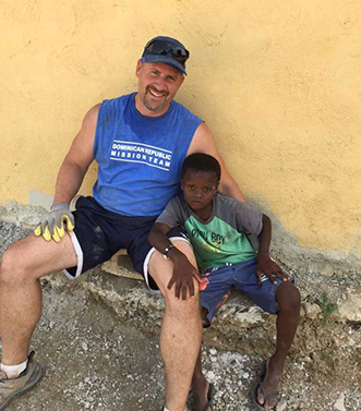 Brian Wallace with the member of a family his church group helped while on a mission trip to Dominican Republic.