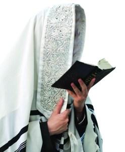 Jewish man praying with tallit and prayer book