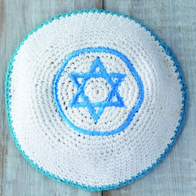 Flat lay of a Knitted kippah with embroidered blue and white Star of David on a wooden table. Jewish lifestyle concept copy space