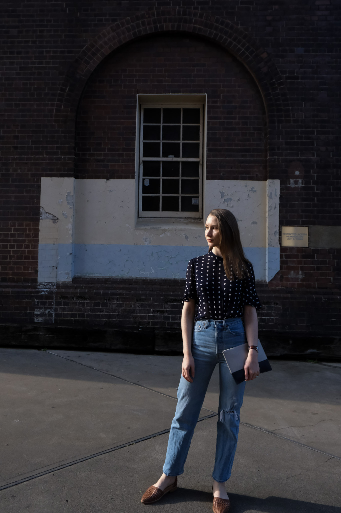 The principle of 30 wears, girl in blue and white polka dot top, levi ribcage jeans and a country road clutch again an industrial background. Minimalist fashion and classic, timeless style. Buying with intention and mindfulness