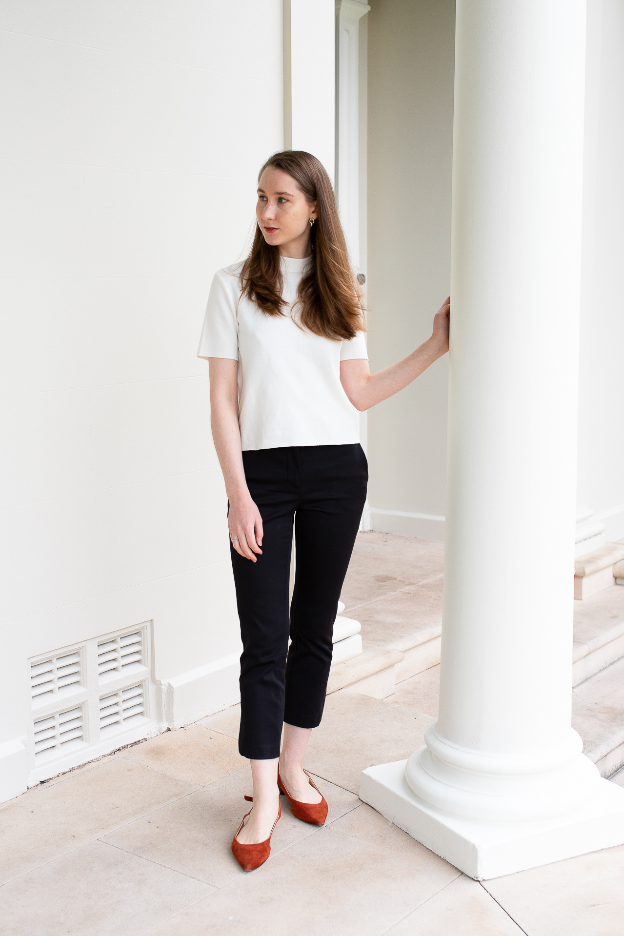 A girl standing in front of white columns wearing a white t-shirt and black pants, minimalist work outfit, simple outfit, white t-shirt, minimalist work outfit ideas. How to prioritise your clothing purchases
