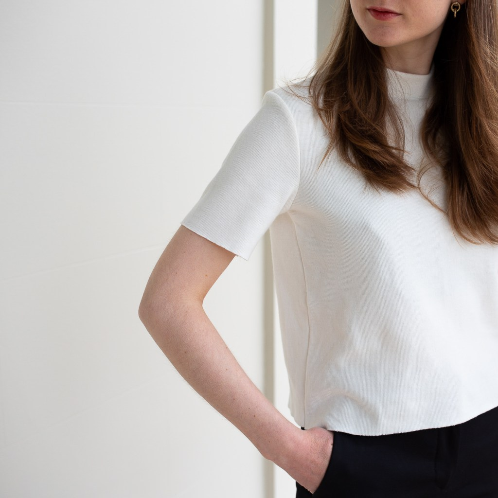 A girl standing in front of white columns wearing a white t-shirt and black pants, minimalist work outfit, simple outfit, white t-shirt, minimalist work outfit ideas