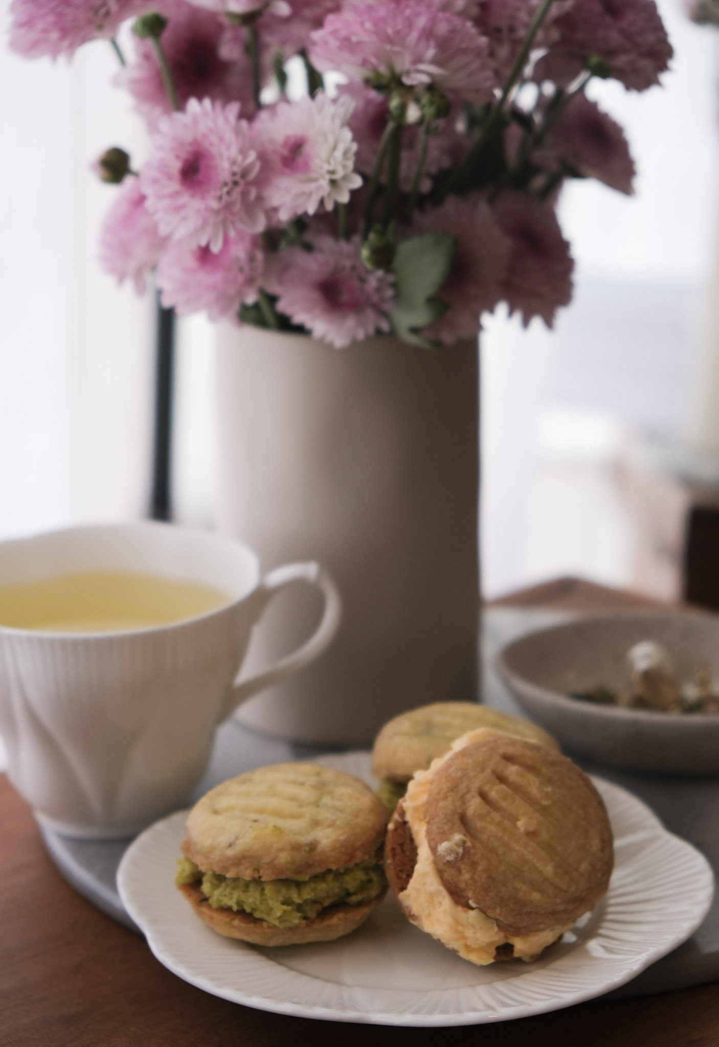 Melting moments, a vase of pink flowers and a tea cup on a coffee table, minimalist decor inspiration, floral arrangements, baked goods