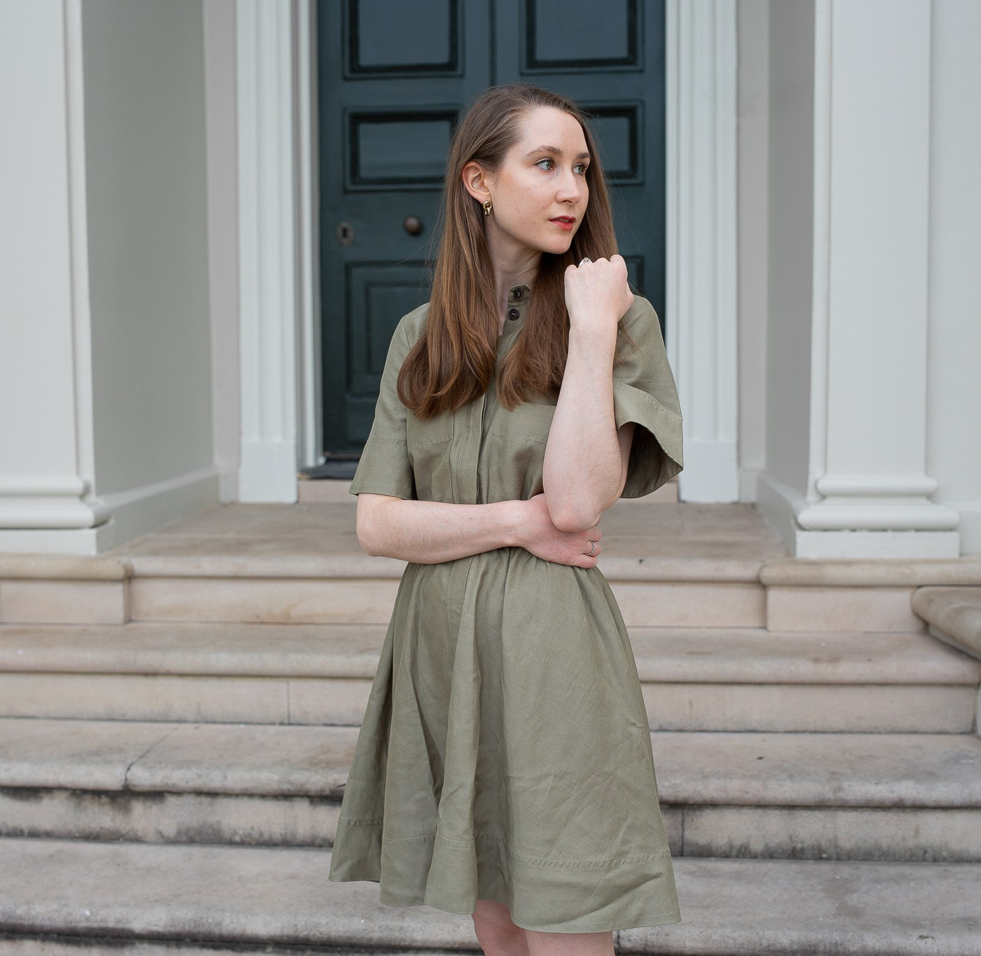 Girl standing in front of a historical building wearing a olive green dress, Hollywood Glamour, Minimalist style inspiration, historical fashion, Regency Core