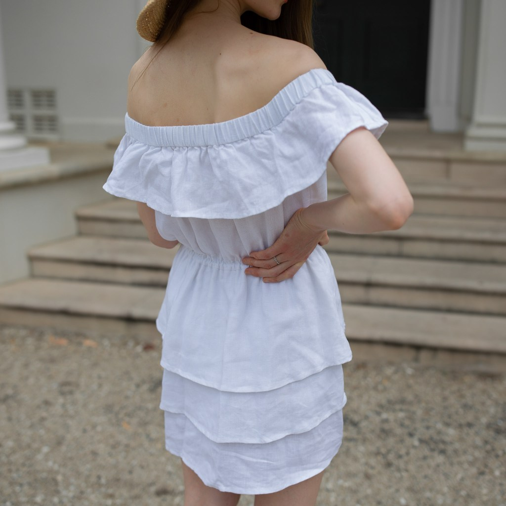 Girl standing in front of a historical building in Sydney wearing a white linen dress. Secondhand September, thrifted outfit, secondhand style, slow fashion, sustainable fashion