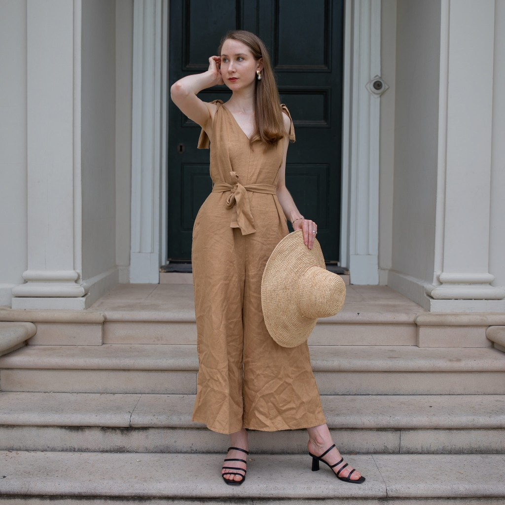 Girl standing in front of a historical building in Sydney wearing a brown linen jumpsuit. Secondhand September, thrifted outfit, secondhand style, slow fashion, sustainable fashion