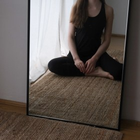 Girl sitting in front of a mirror wearing Boody active wear tank top and Dharma Bums black 7/8 scallop leggings. Sustainable activewear review, minimalist active wear, sustainable brands