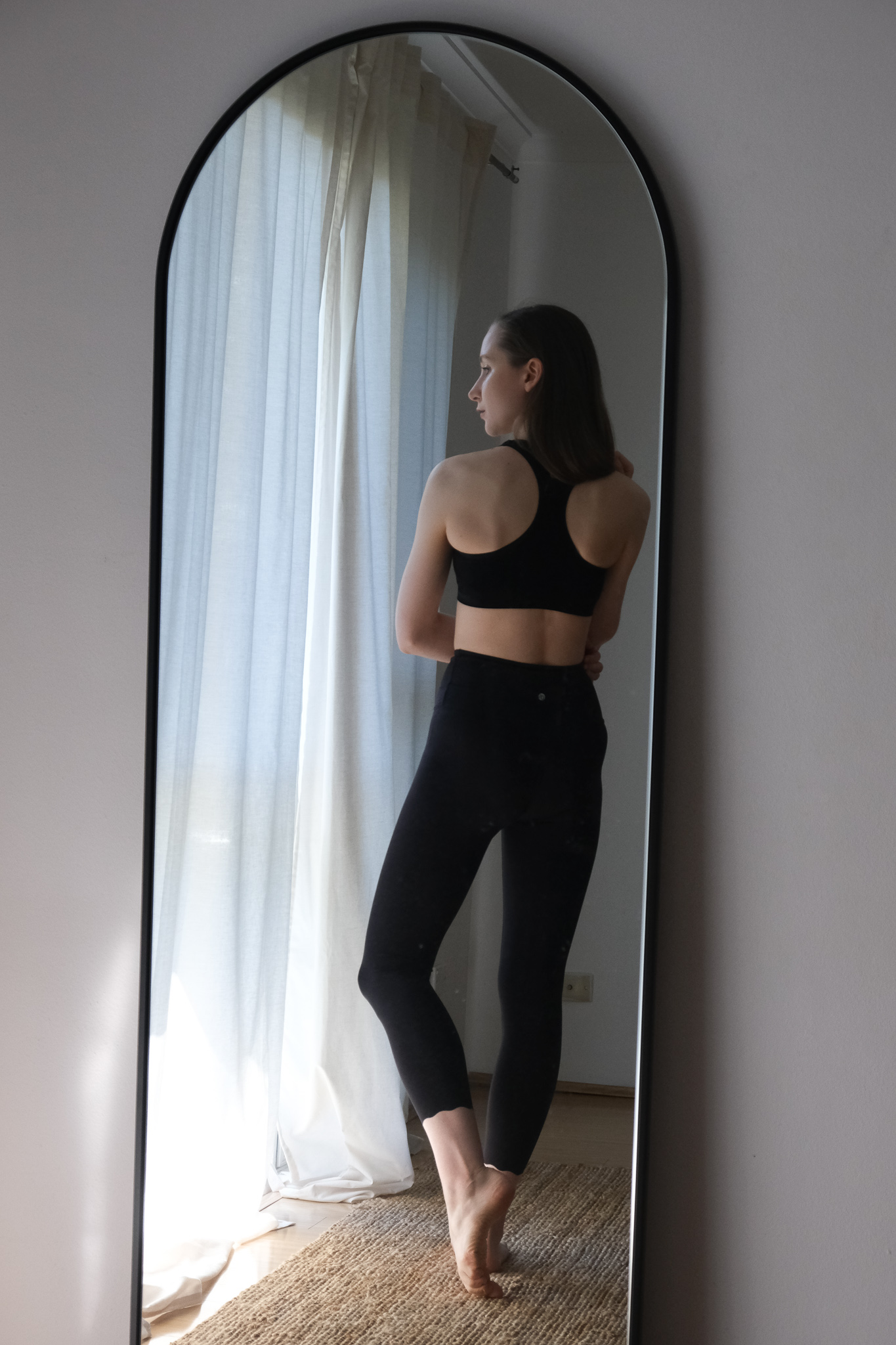 Girl standing in front of an arch mirror wearing Boody racer back sports crop top and Dharma Bums black 7/8 scallop leggings. Sustainable activewear review, minimalist active wear, sustainable brands