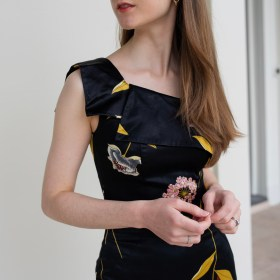 Girl wearing a floral dress with a bold print and asymmetrical neckline.