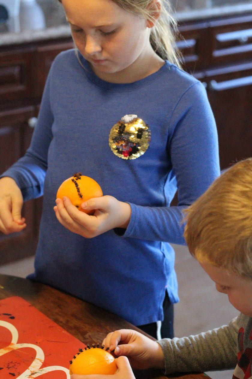 Kids putting Cloves into Oranges