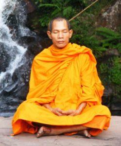 Thai Abbot meditating near waterfall