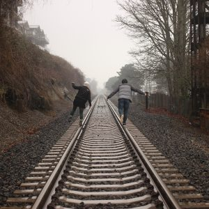 two friends walking together on railroad tracks