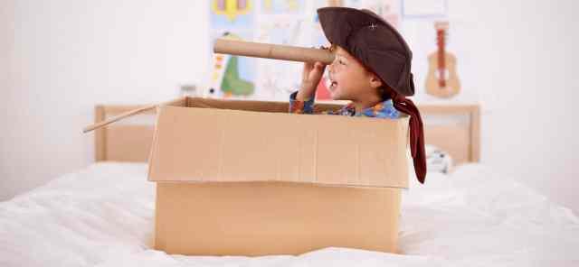 Criatividade: criança imagina ser marinheiro em caixa de papelão.