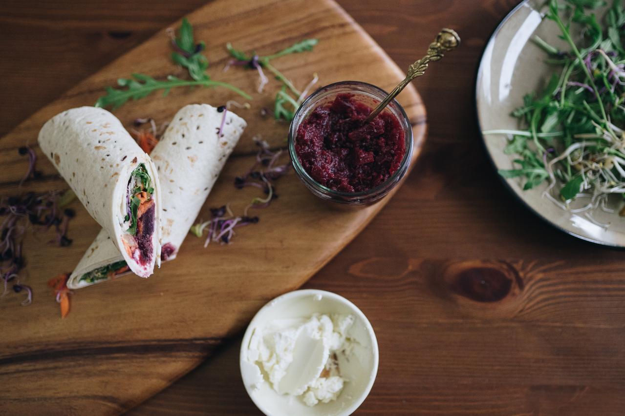 Tortilla Wrap mit Gemüse und Chutney gefüllt auf einem Holzbrett