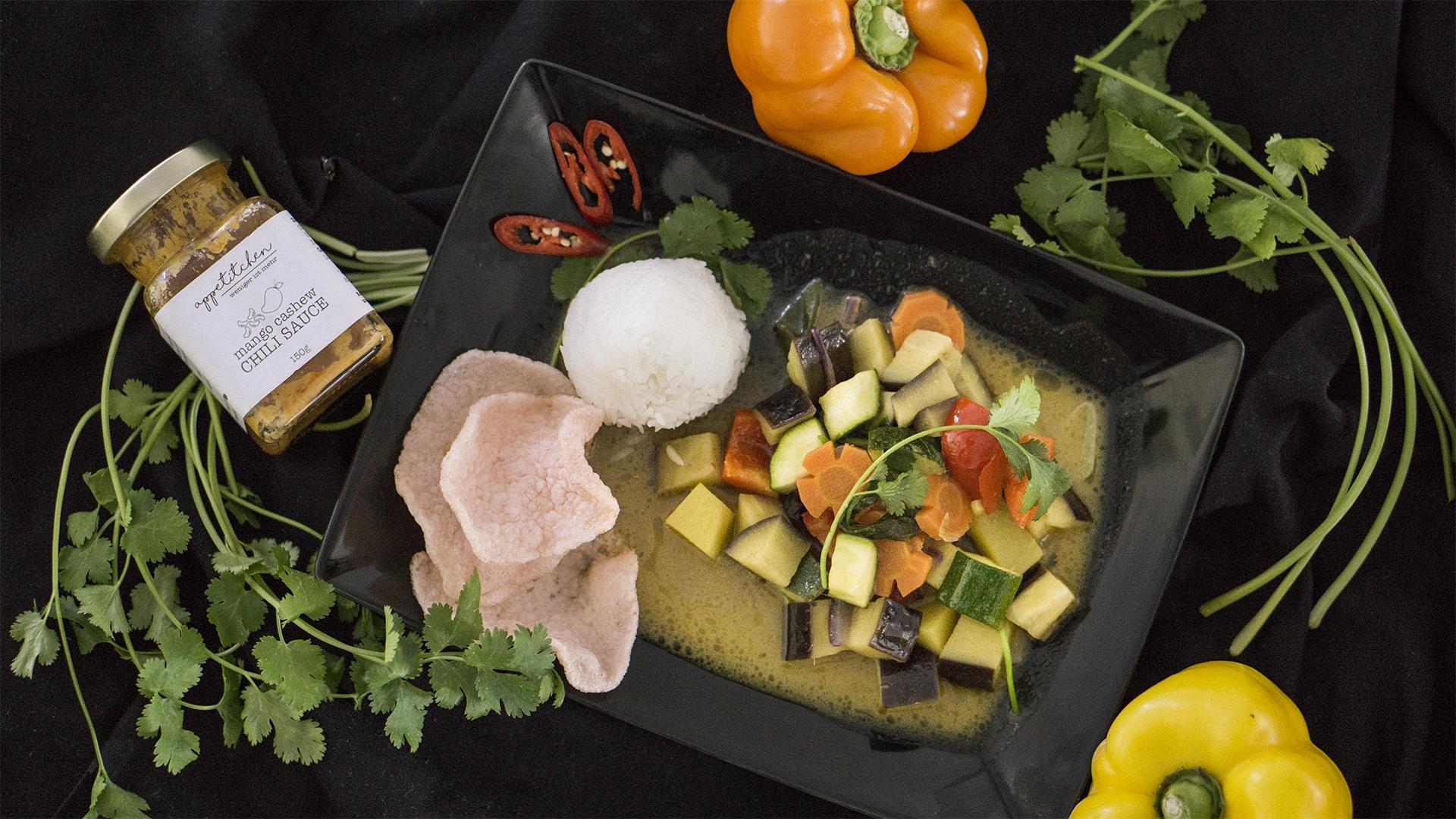 Ein Teller mit Gemüse Curry und Reis mit Chili Sauce