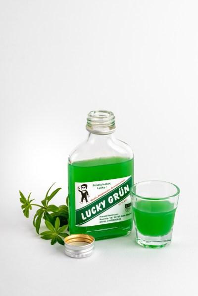 Eine kleine geöffnete Flasche Wodka Waldmeisterlikör mit Waldmeisterpflanze und Shotglas