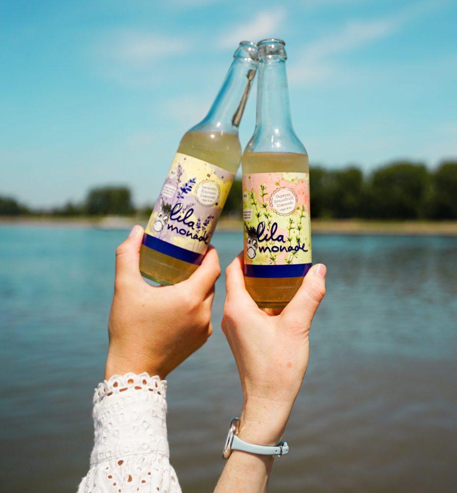 LiLamonade zwei Hände mit beiden Limonaden am Wasser