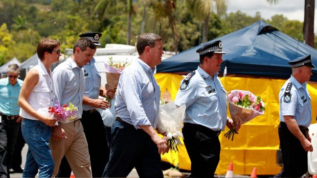 Acting Premier Tim Nicholls and senior police walk past the Cairns house where eight children died.