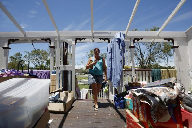 Yeppoon resident Demelza Bischoff walks onto the roofless veranda of her home on Saturday, after it was damaged during Cyclone Marcia.