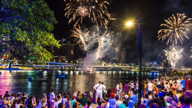 Crowds at South Bank watch as the skies above Brisbane explode with New Year's Eve fireworks.