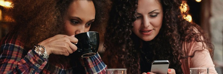 Young friends sitting in a cafe looking at a smartphone. One woman drinking coffee and another holding mobile phone.