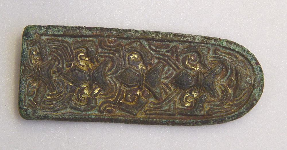 Tongue-shaped brooch; gilt copper alloy; high relief Borre style ring chain and interlace on front; plain border; back tinned; pin fittings; traces of iron pin and grass stems in corrosion; slightly bent.