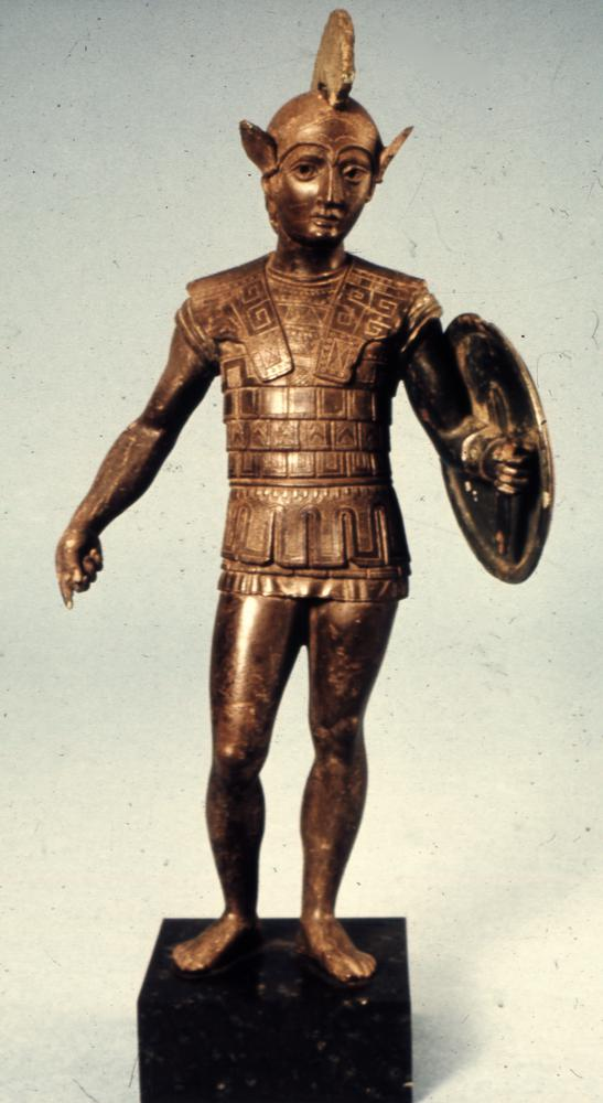 Bronze votive statuette of a warrior with a shield, wearing an Attic helmet and a scale cuirass. The statuette was cast whole, with the shield and helmet-crest made separately. The crest is shown attached in this image.  The stance reflects Greek Sculpture of the late 5th century BC, and the style is related to the bronzes of central and northern Etruria.