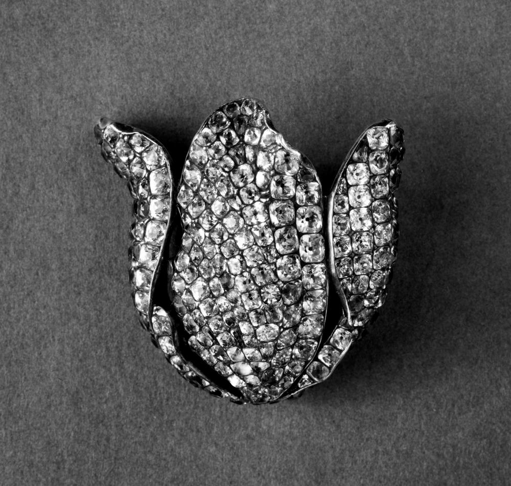Dress ornament in the form of a tulip flower-head.Silver in very high relief, hollowed out at the closed back, set with calibré-cut pastes. The later pin probably replaces sewing links; .