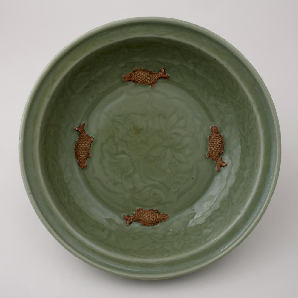 Longquan porcelain dish with flattened mouth rim, and thick inclined foot rim. The dish has a grey-green glaze. There is a lotus spray in the centre surrounded by a scroll, and four unglazed fish around the interior.
