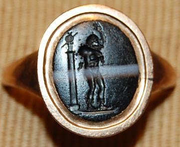 Banded onyx gem engraved with Seilenos moving to the left, with a wine-skin on his shoulder and his right hand raised; behind is the Palladion on a column.
