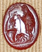 Sard gem engraved with Faustulus, with a tunic, skin cloak and staff, finding the she-wolf and Romulus and Remus under a rock, above which is a tree and a helmeted head (?).