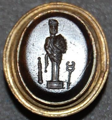 Brown sard gem, nearly opaque, engraved with a bearded terminal figure of Herakles; in the field is a club and a caduceus.