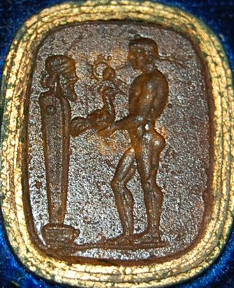 Gem of glass paste imitating sard, engraved with a terminal figure of Hermes, before which stands a youth holding a wreath and palm-branch in his left hand, and a cock on his right.