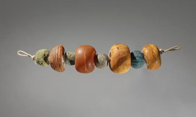 Eight beads: three amber; three monochrome glass; one melon; also one amber hemispherical spindle-whorl with concentric grooves.