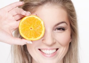 Lady holding up sliced orange