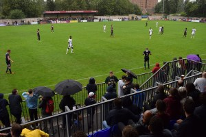 Fans shelter from the late-summer rain